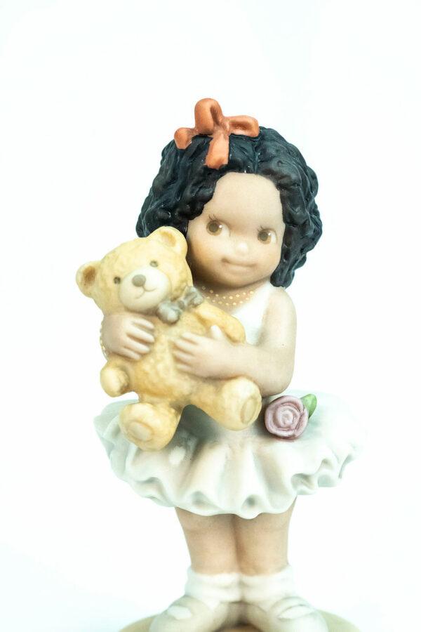 figurine, little girl holding teddy bear, closeup