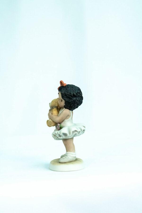figurine, little girl holding teddy bear, left