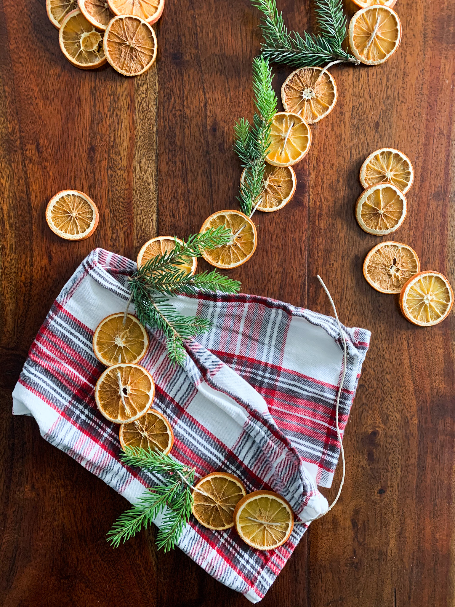 dried orange garland with pine on the table and a plaid towel