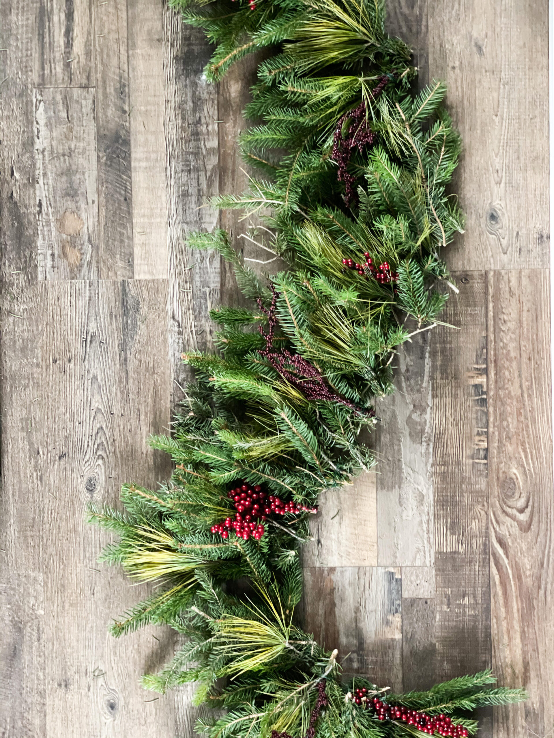 Real pine made into garland with red berries laying on the ground