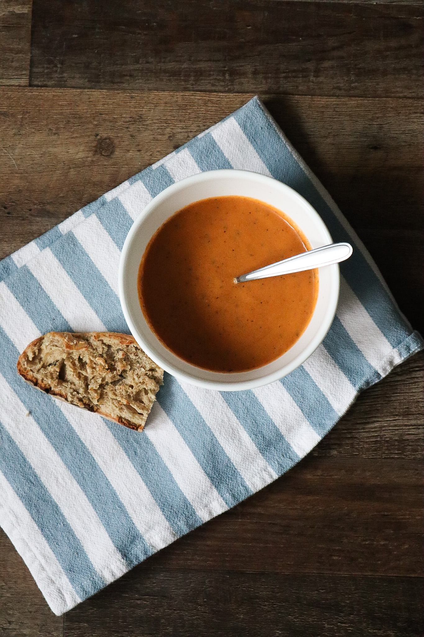 tomato soup paired with a slice of bread on a striped towel
