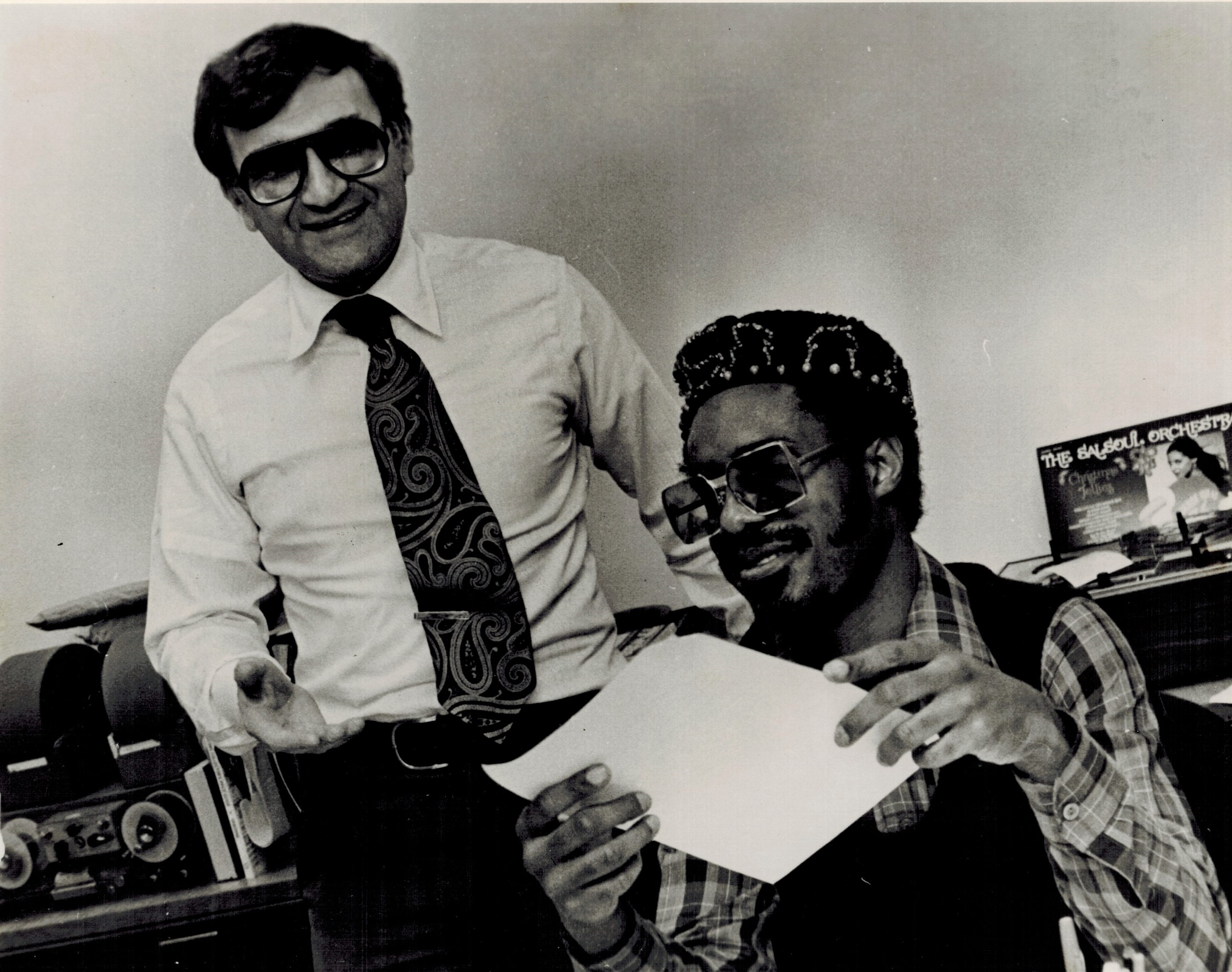 Stevie Wonder jokes in Rick Sklar's office, pretending to read WABC's ratings.