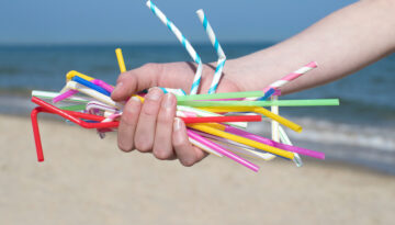 bio plastics straws Close Up Of Hand Holding Plastic Straws Polluting Beach
