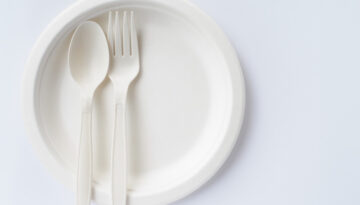 bio plastic spoon and fork on disposable plate