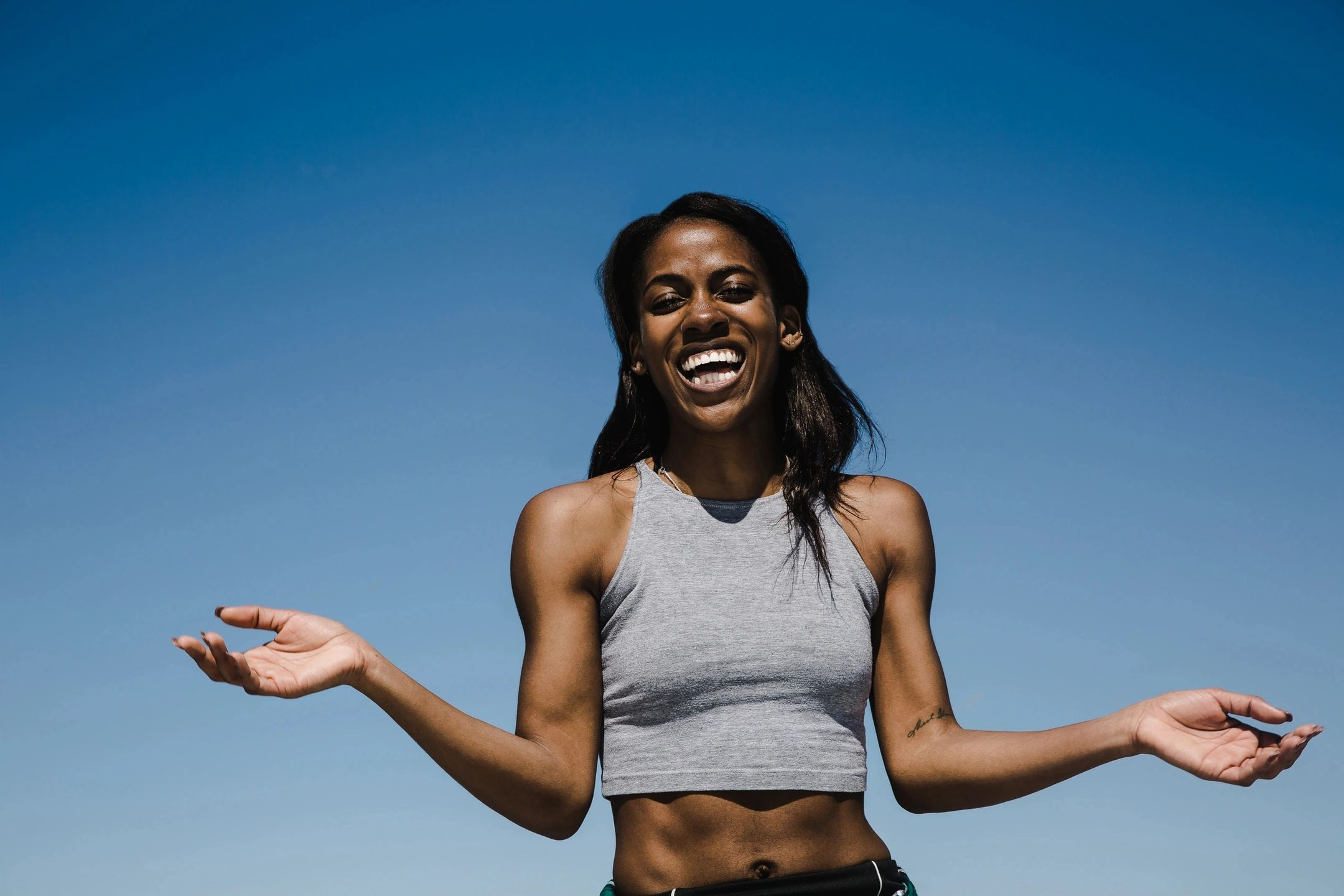 Black woman athlete smiling with a blue sky