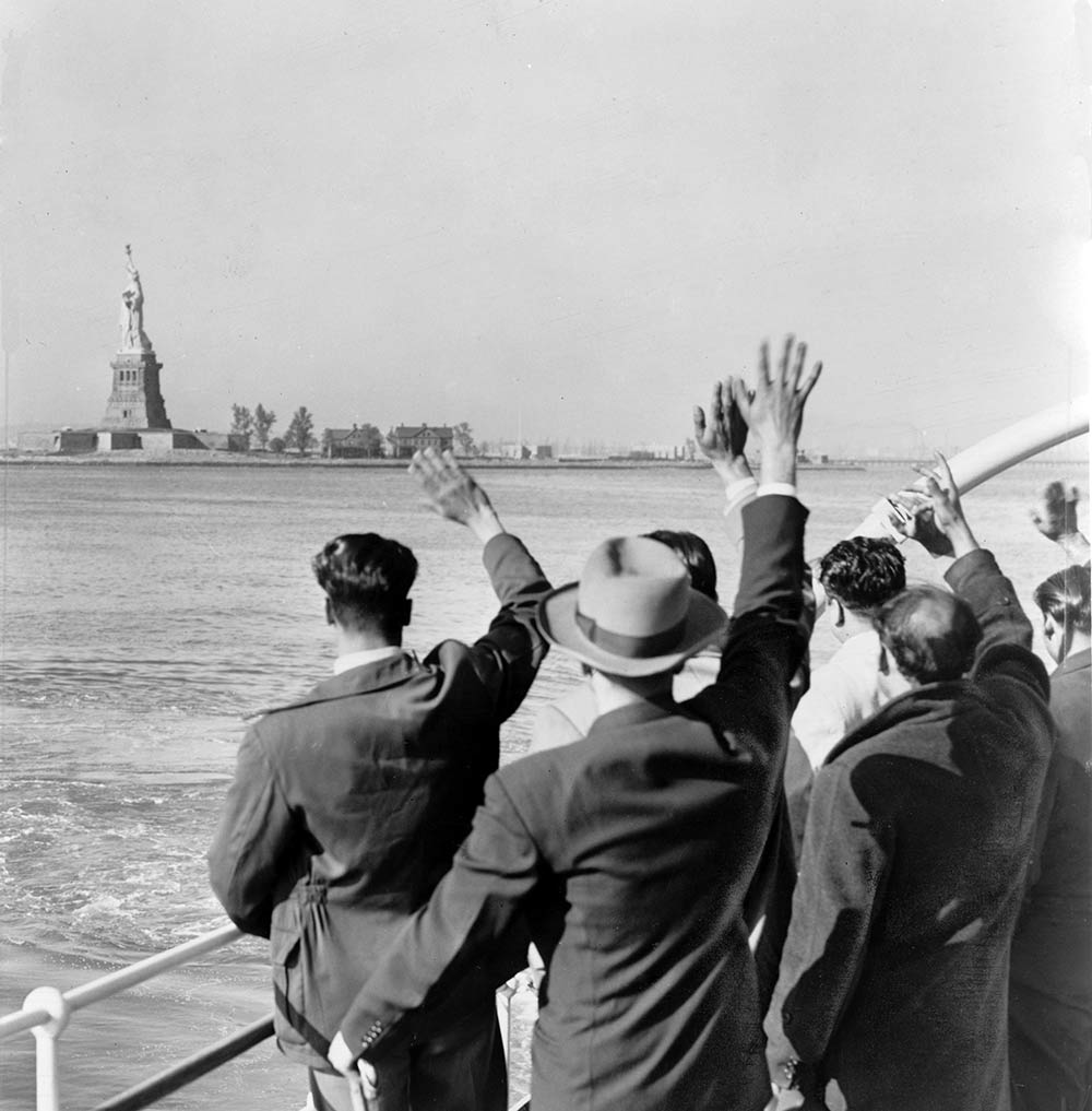 Tamp Immigration Attorney - Photo of people on boat waiving flags at the Statute of Liberty