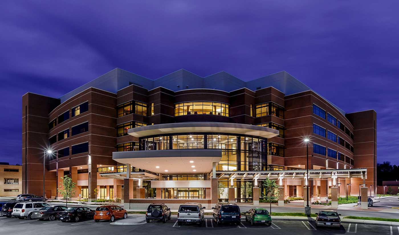 A night view of the atrium entrance illuminates the hospital exterior.