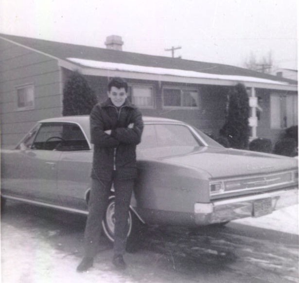 George poses in front of his uncle's car shortly after arriving in the United States.
