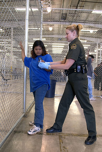 A detainee is patted down by a CBP Agent.
