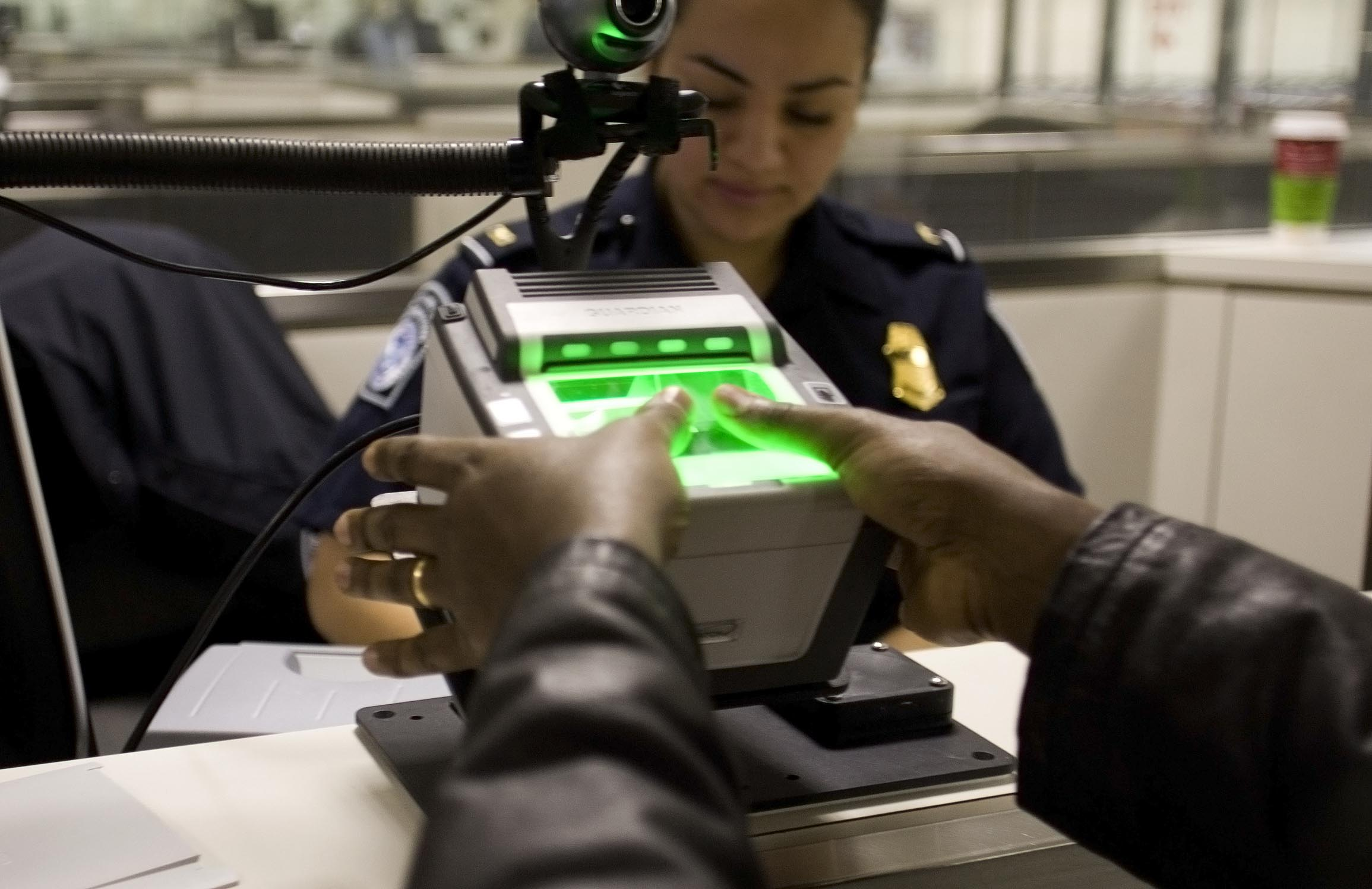 A traveler arriving at Washington Dulles International Airport Monday uses the new US-VISIT mechanism that records all 10 fingerprint images.