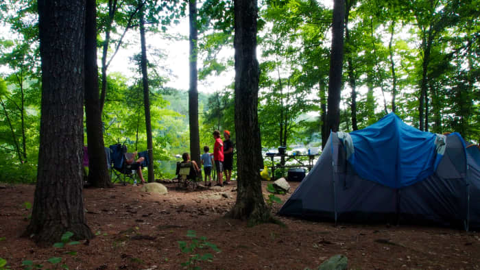 Family on shaded campsite with blue tent and view of lake on a sunny day