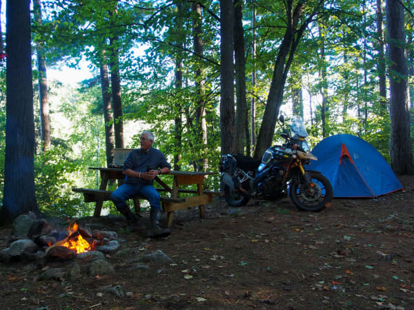 motorcyclist sitting at campfire with Suzuki VStrom and tent