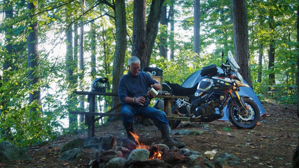 man sitting at picnic table in front of fire pouring coffee. motorcycle and tent in background. view of lake.