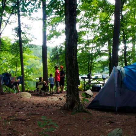 view of campsite 5 with children, blue tent and view of lake