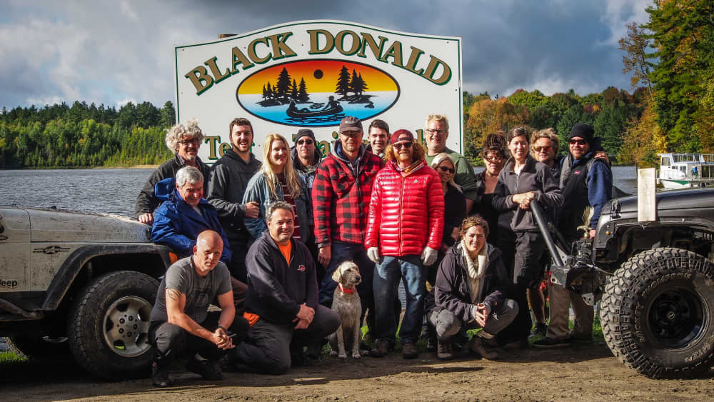 Eastern Ontario Trail Blazers group photo in front of Black Donald Tent and Trailer Park sign in front of lake
