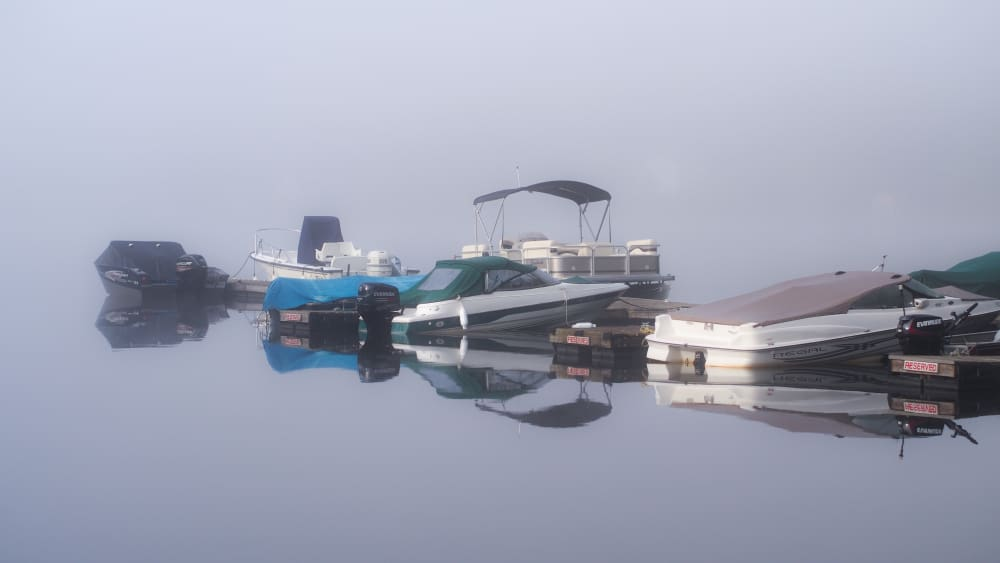 boats at the dock surrounded in fog
