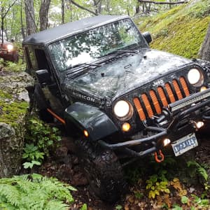 Jeep Rubicon offroad in the woods near black donald tent and trailer park