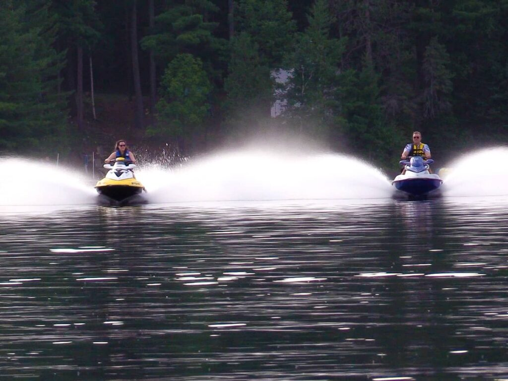 two jet skis speeding across the water