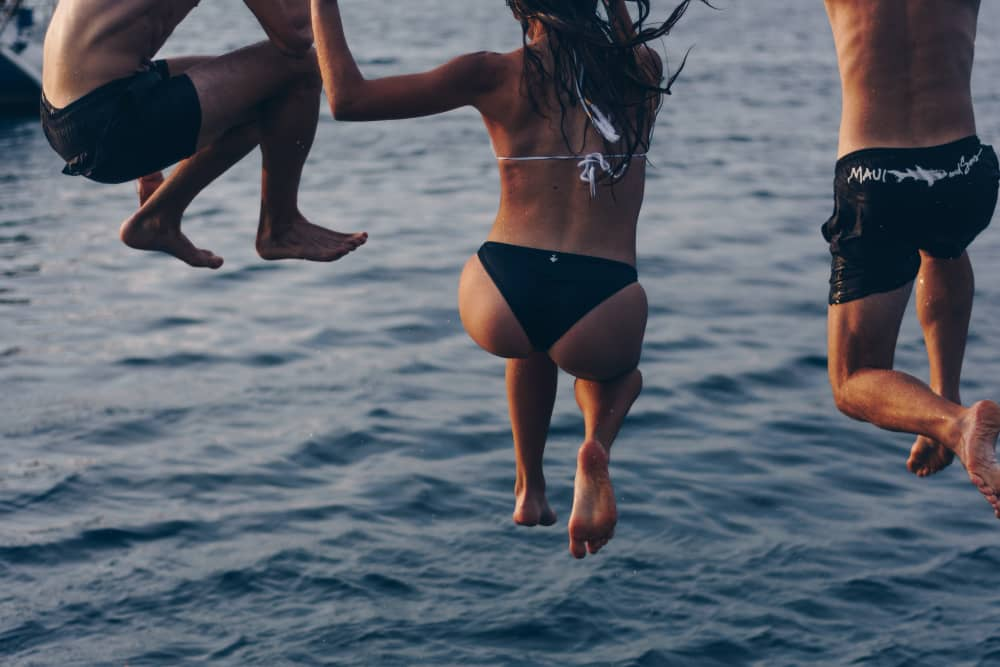two men and a woman jumping off the dock into the water