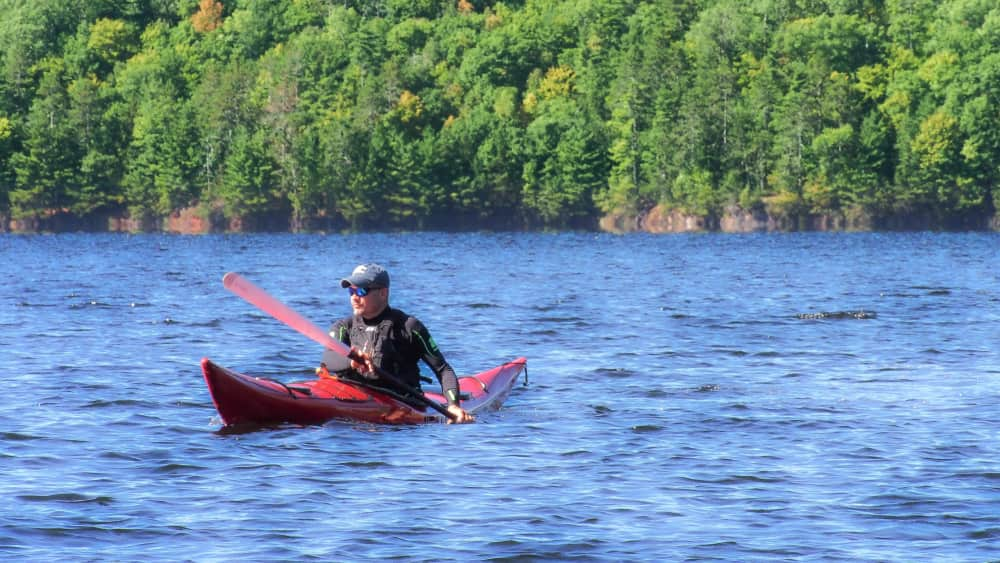 A kayaker paddling across the lake on a sunny day