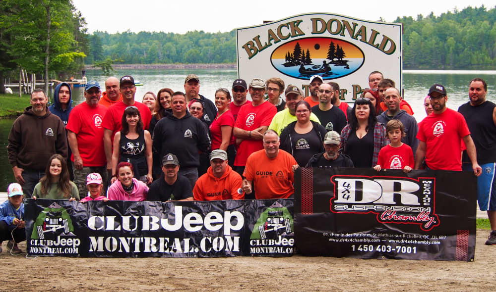 group photo of the montreal jeep club in front of the sign and dock at Black Donald Tent and Trailer Park in Ontario
