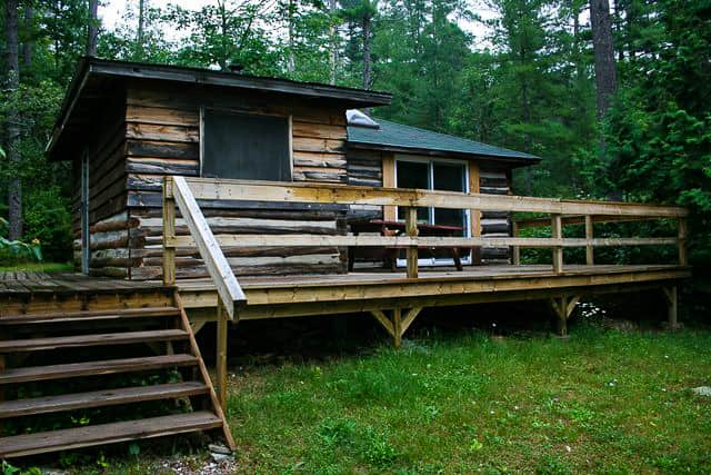 Front of Log Cabin on Norcan lake showing large deck with picnic table