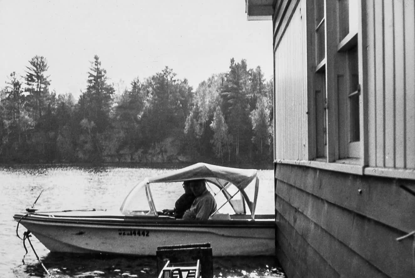 motorboat towing a house down the madawaska river in 1971