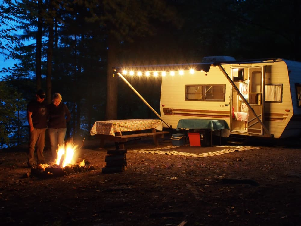 couple standing around campfire with camper in background