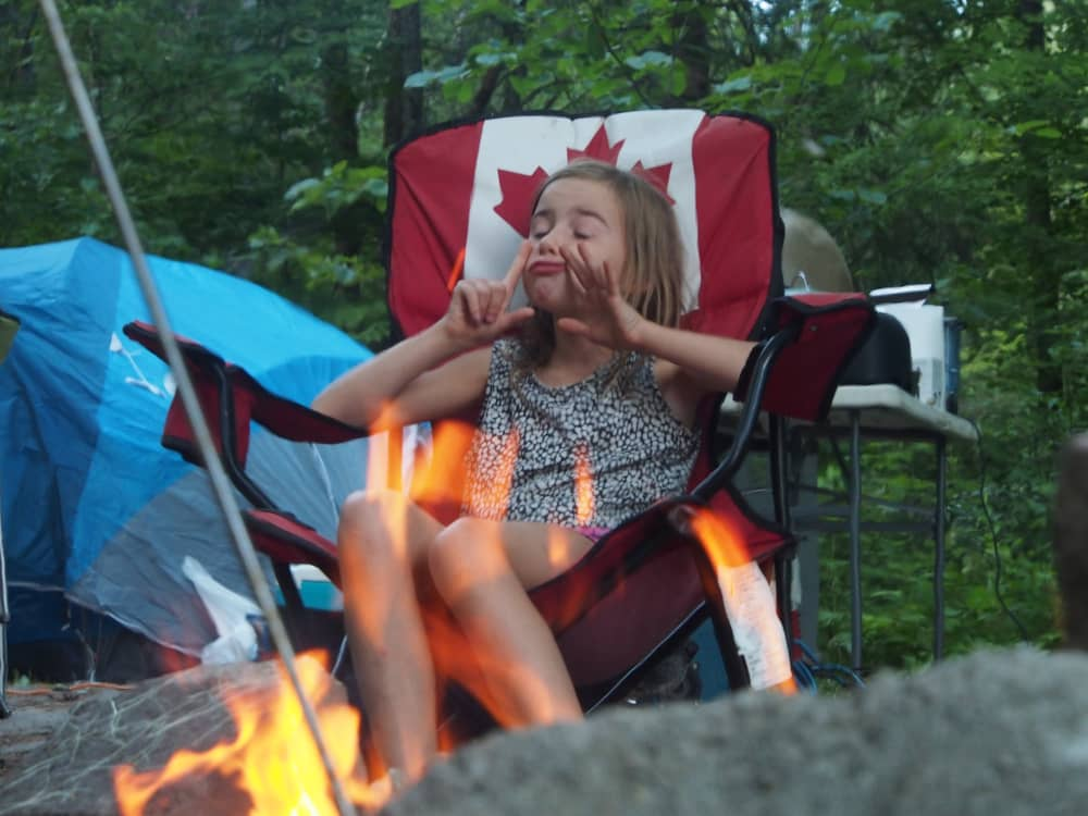 Little girl at campfire making a funny face