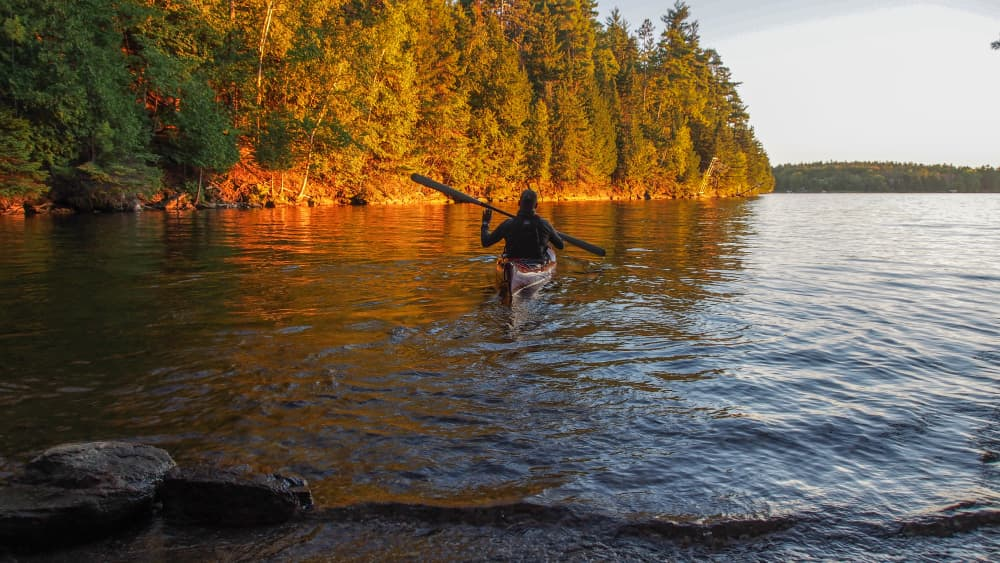 A kayaker paddling away from shore in a golden sunset