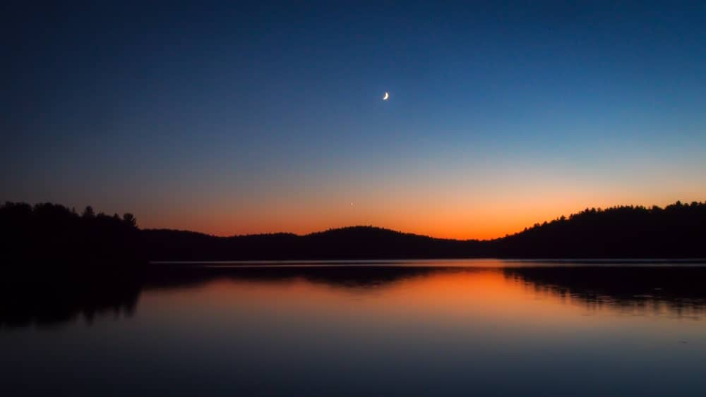 a silver moon in the sky over the lake at sunset