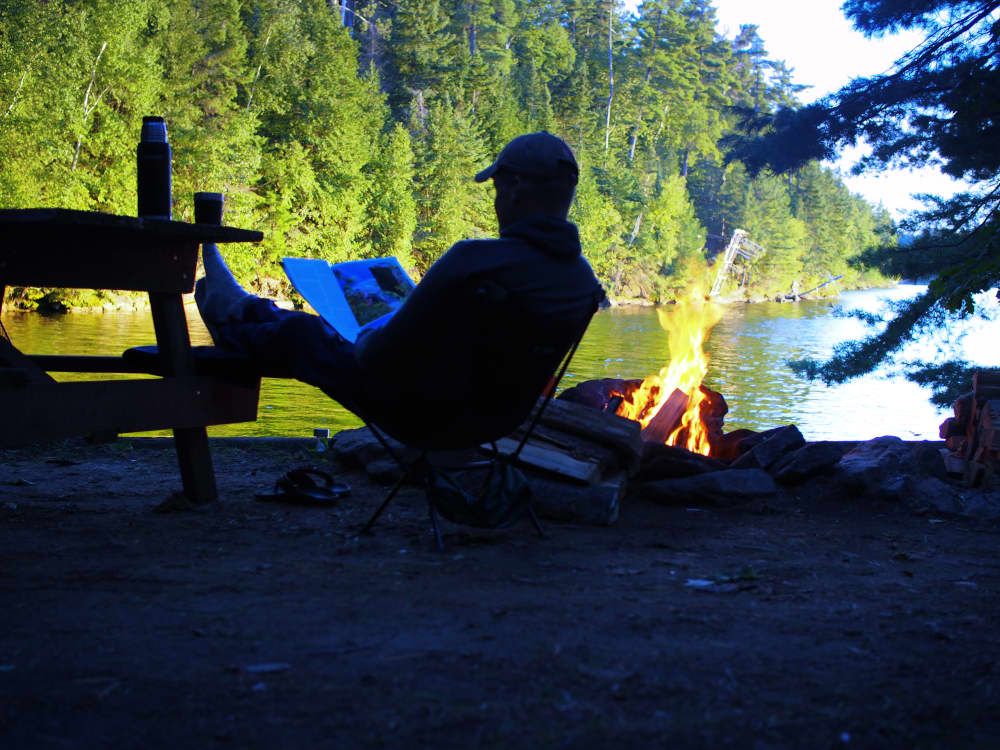 a man sitting by a campfire at the waters edge reading a magazine at the best campground in ontario