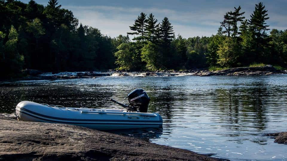 a zodiac pulled up on the rocks at the end of centennial lake where the rapids are