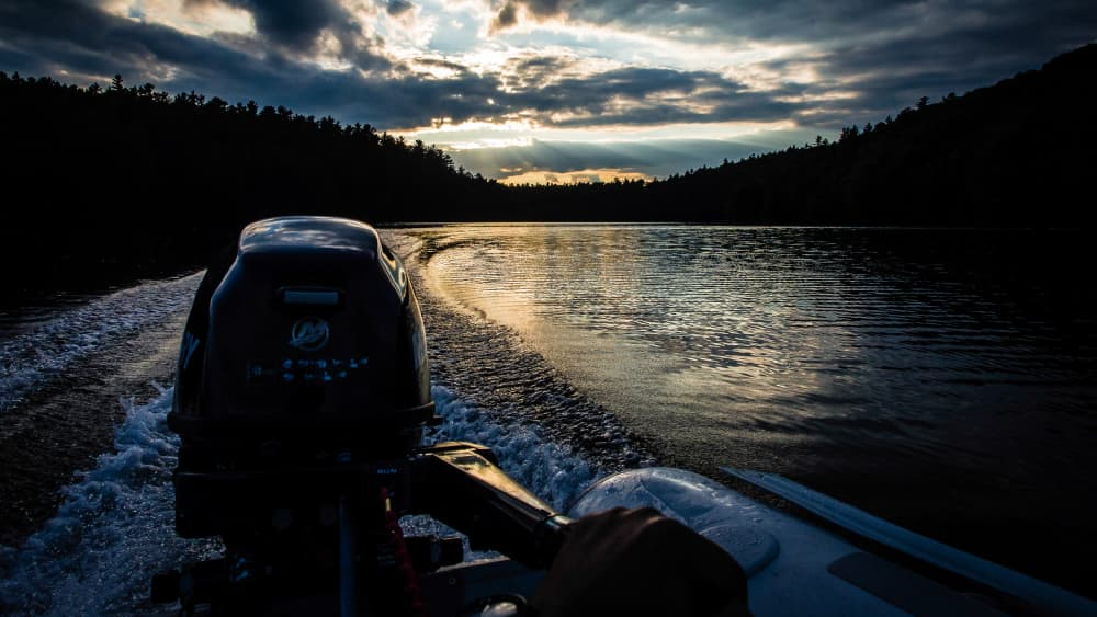 wake behind a zodiac with a 9.9 Merc outboard and the sunsetting over the water