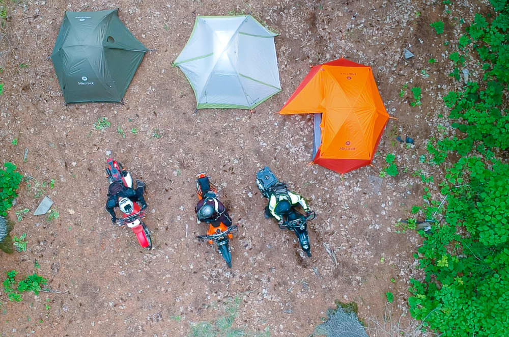 aerial view of 3 motorcycle riders parked in front of tents at black donald tent and trailer park