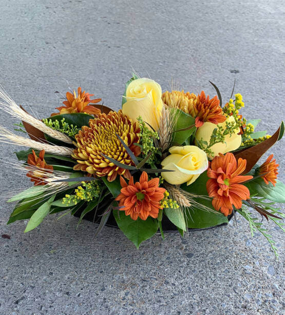 An image of an autumn table arrangement, with yellow roses, sunflowers and daisies