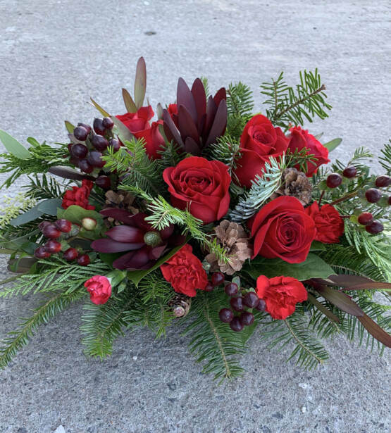 A red and green Christmas arrangement with red roses and pine branches