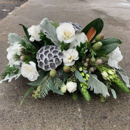 A picture of a white christmas arrangement. The Arrangement features white roses, greenery and berries