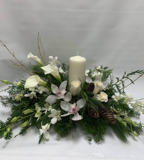 An image of a white and green christmas arrangemnet feauring a white candle, orchids, calla lilies and pinecones