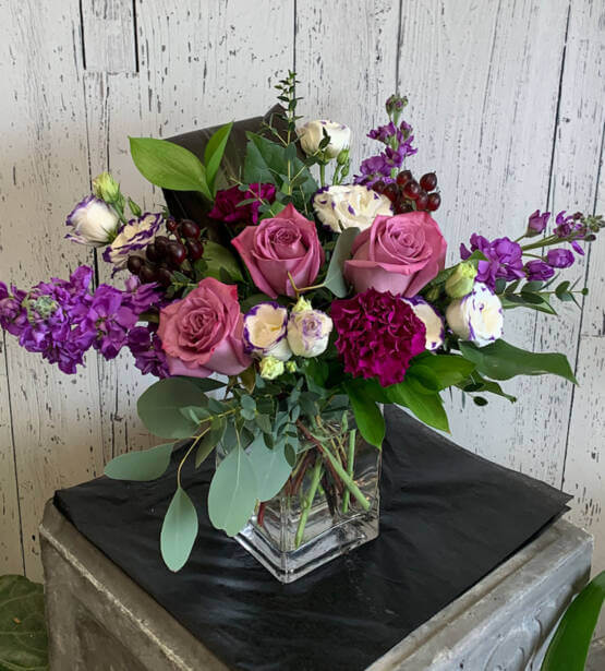 An image of a pink, purple and green flower arrangement in a glass vase