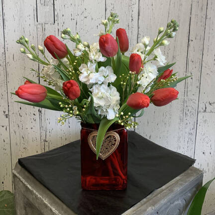 An image of a valentines arrangement with red roses in a heart vase