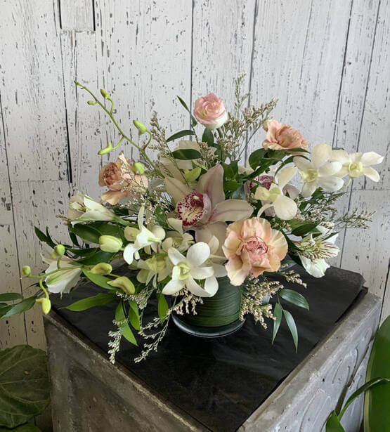 An image of a white and pink flower arrangemet with white orchids and pink roses