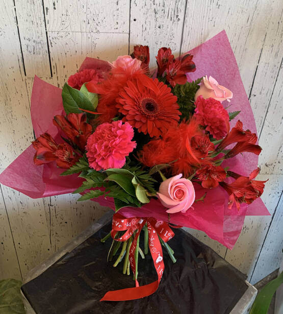 An image of a red and pink valentines bouquet with roses, Gerbra's and carnations