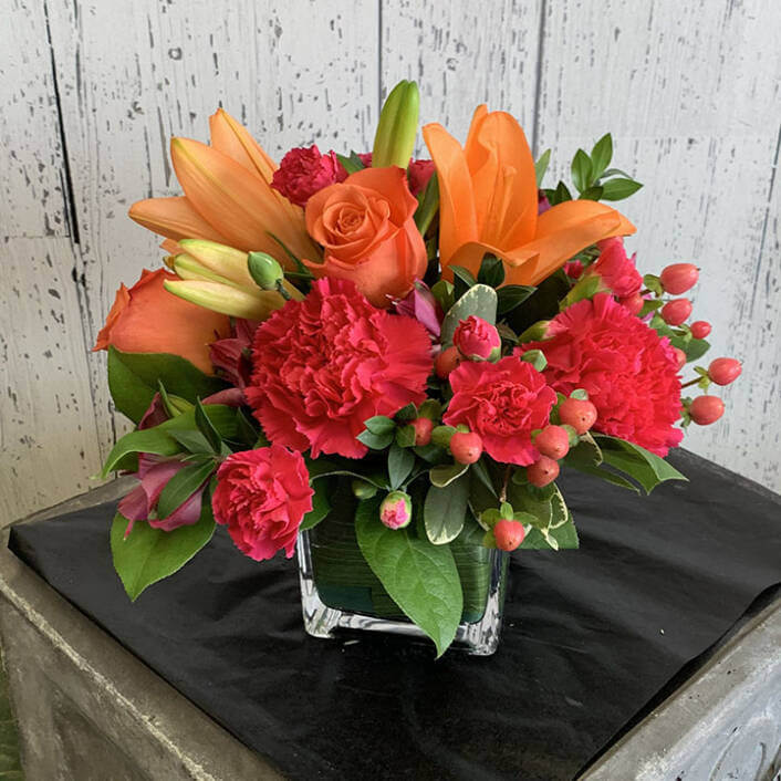 An image of a red and orange flower arrangement with lilly's, roses, and carnations
