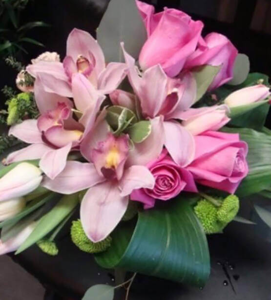 An image of a pink floral arrangement with orchids and roses