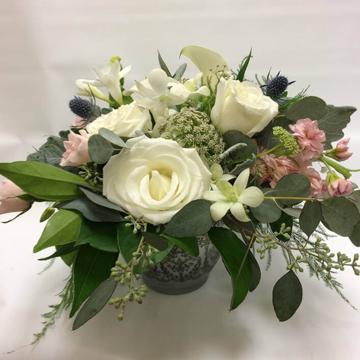 An image of a white and pink floral arrangements with greenery
