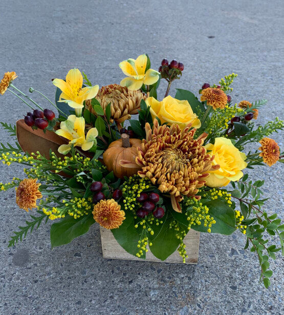 an image of a fall arrangement, yellow and orange in colour with a orange pumpkin in the middle