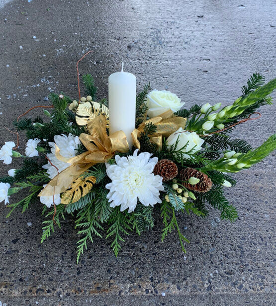 An image of a white gold and green Christmas arrangement with a white candle