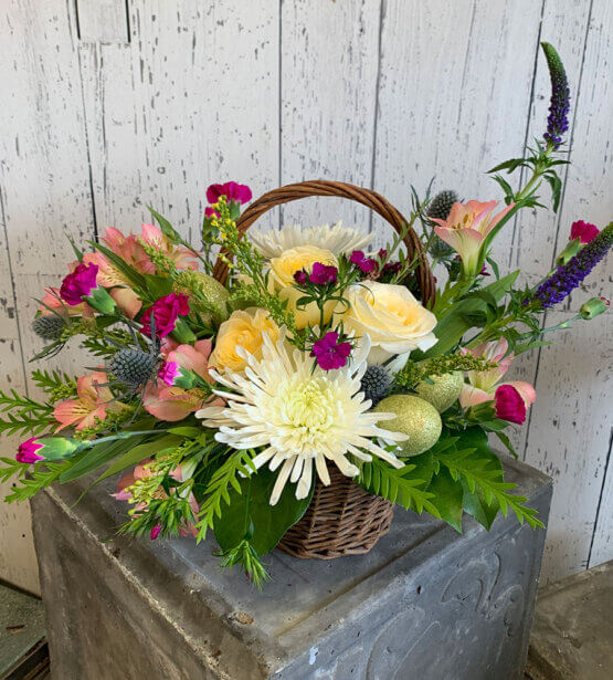 Spring coloured flower arrangement in a wicker basket