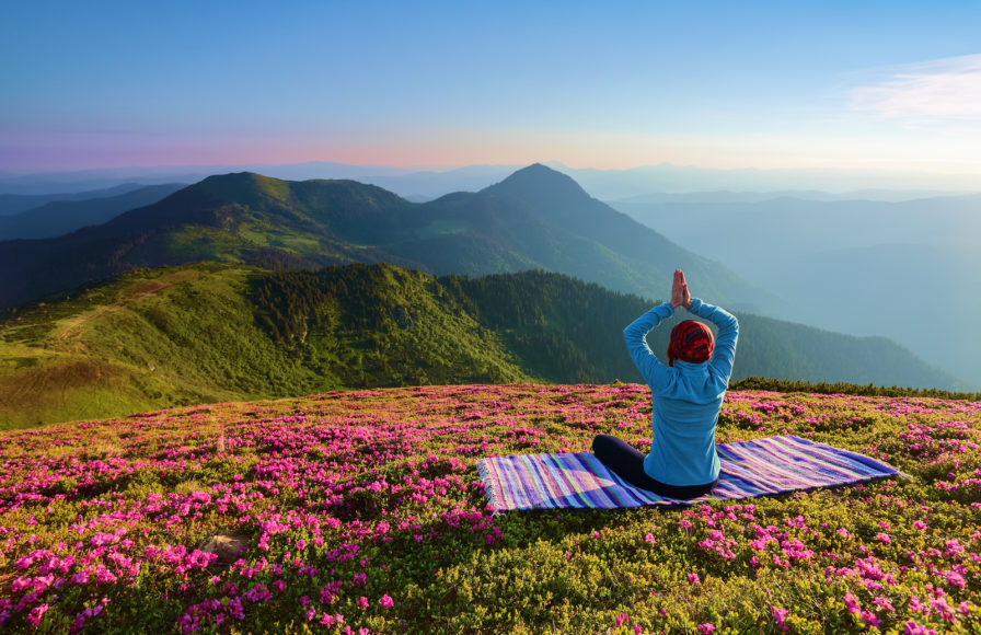 On the lawn among the rhododendron flowers the yoga girl is sitting in the pose on the colorful rug. Meditation. The landscape with the mountains in the fog. Nice summer scenery.